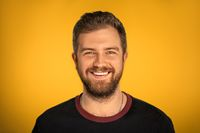 Young white man smiles on a yellow background in the studio. Man with beard in black jacket. High quality photo