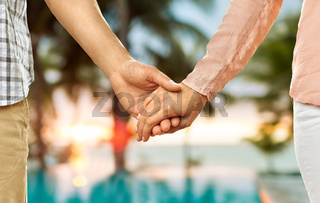 close up of couple holding hands over exotic beach