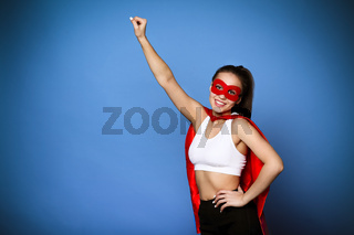 Cheerful woman in superhero cloak holding arm raised
