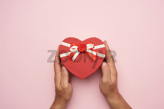 male hand holding a red cardboard box with a bow on a pink background