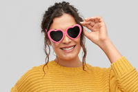 smiling young woman in heart-shaped sunglasses