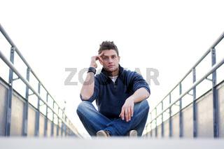 Handsome young man sitting between handrails in walkway