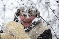 A frozen man covered in snow in winter smiles and looks at the camera. The first snow fell. A man in a fur hat in cold weather.