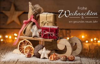 Weihnachtsgruß Frohe Weihnachten - Schlitten mit Päckchen und Gebäck im Schnee