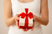 Woman's hands holding present with red ribbon from close up