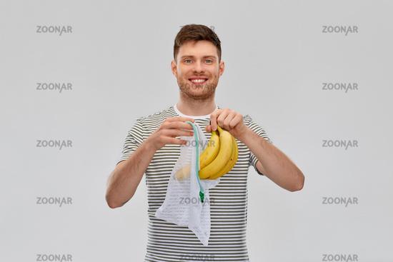 smiling man putting bananas into reusable net bag