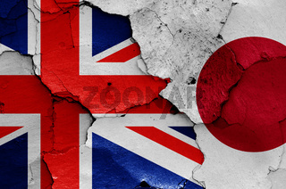 flags of UK and Japan painted on cracked wall