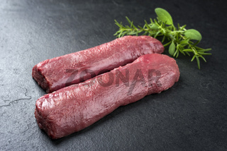 Raw dry aged venison tenderloin fillet steak natural with herbs offered as closeup on a modern design board