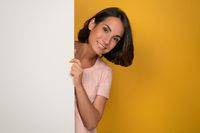 Pretty young woman peeking out of empty banner looks at camera as if watching a family. Smiling young model in a light pink t-shirt looking out of white blank. Isolated on a yellow background