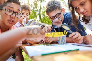 Gruppe Kinder mit Lupe lernt über Pflanzen