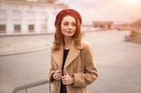 Charming french young woman in an autumn beige coat and red beret standing holding the edges of the coat trying to button it urban city background. Toned photo