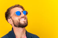 Close up portrait of funky young bearded hipster man in blue sunglasses smiling brightfully on a yellow background. Copy space. Looking up and laughing.