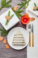 Napkin in the form of a Christmas tree on a plate on white tablecloth with gifts and decorations with fir sprigs and gingerbread cookies