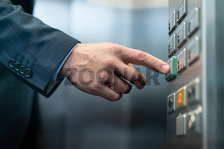 Businessman presses button with braille for blind. Close up shot of Caucasian male hand pressing key for closing doors in elevator of business center
