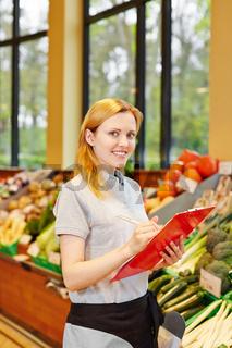 Verkäuferin mit Klemmbrett im Supermarkt
