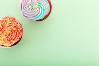 High angle view of two colourful cupcakes with sprinkles on green background