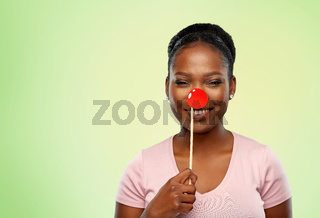 happy african american woman with red clown nose