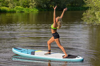Young woman standing arms up on SUP