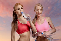 Two women drinking water after fitness exercise