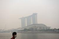 Singapur, Republik Singapur, Mann mit Atemschutzmaske vor im Smog verschleiertem Marina Bay Sands Hotel