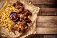 Appetizing roasted chicken wings and french fries with barbecue dip, served on baking paper