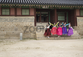 Seoul, South Korea - September 4 2017: five korean tourist women in traditional Hanok clothes jumping from the stairs of a building in Gyeongbokgung Palace