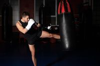 Muscular handsome kickboxing fighter giving a forceful kick during a practise round with a boxing bag.