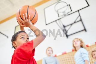 Afrikanischer Grundschüler wirft Basketball im Sportunterricht