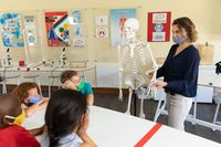 Female teacher wearing face mask using human skeleton model to teach students in class