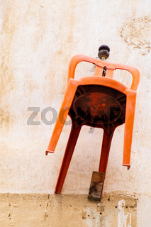 Orange chair hanging on the wall of a traditional house in the old city of Nicosia, Cyprus