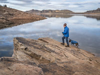 hiker with pitbull dog on a shore of lake at foothills of Rocky Mountains