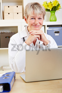 Lächelnde Ärztin am Schreibtisch