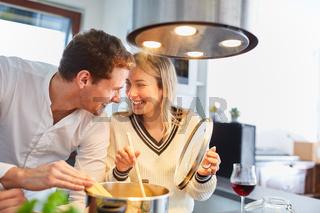 Glückliches Paar in Küche beim Nudeln kochen