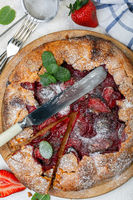 Pie with strawberries, sprig of mint, sprinkled with powdered sugar.