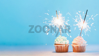 Two cupcakes decorated with sparklers, copy space