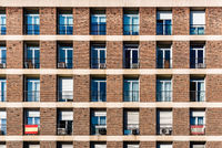 Full frame of brick facade of residential building with array of rectangular windows
