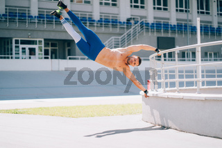 Young athletic man performs gymnastic elements - human flag.