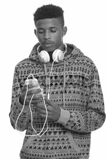 Young handsome African man using mobile phone while wearing headphones around neck