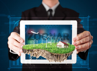 Businessman presenting a perfect ecology land with a house and windmills