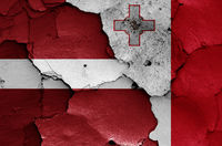 flags of Latvia and Malta painted on cracked wall