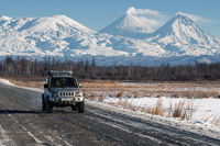 Japanese Sport Utility Vehicle Suzuki Jimny driving along road on background winter landscape