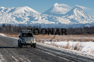 Japanese Sport Utility Vehicle Suzuki Jimny driving along road on background beautiful winter landscape travel destinations