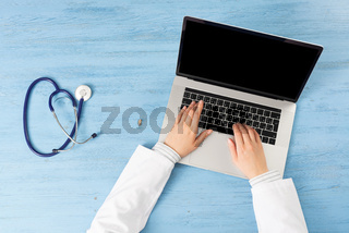 Top view of doctor hands typing at laptop