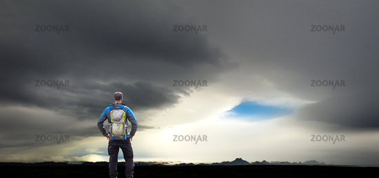 Man Hiker watching huge storm and dark silhouette mountains in Iceland. Icelandic highland.