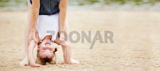 Mädchen macht Handstand am Strand