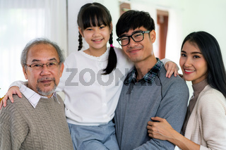 Happy multigenerational asian family portrait in living room
