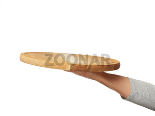 woman holding empty round wooden pizza board in hand