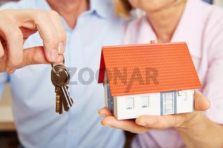 Hände halten Haus und Schlüssel