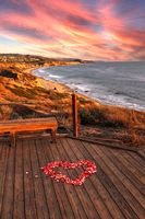 Sunset over Crystal Cove State Park Beach and a heart of rose petals on a wooden boardwalk that over
