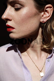 Side portrait of attractive young woman with red lips wearing golden jewellery. Vertical close-up of beautiful woman.